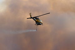 NINGI, AUSTRALIA - NOVEMBER 9 : Waterbomber helicopter with full load heading to fire front into clouds of smoke November 9, 2013 Stock Image