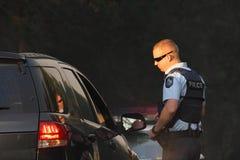 NINGI, AUSTRALIEN - 9. NOVEMBER: Nicht identifizierter Polizeirichtungsverkehr weg von Buschfeuerfront, wie sie Häusern am 9. Nove Lizenzfreie Stockfotografie
