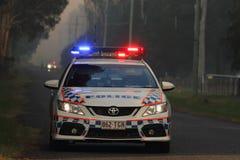 NINGI, AUSTRALIEN - 9. NOVEMBER: Polizeiholdingschnur vor Buschfeuerfront, wie sie Häusern am 9. November 2013 in Ning sich nähert Stockfotos