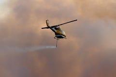 NINGI, AUSTRALIEN - 9. NOVEMBER: Waterbomber-Hubschrauber mit der vollen Last, die vorangeht, um Front in Rauchwolken am 9. Novemb Stockbild