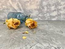 Ningún amor Las rosas amarillas se secaron y cayeron en una botella de cristal azul, fotografía de archivo