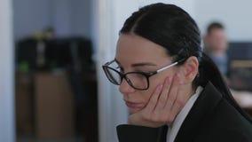 Ningunas ideas, mujer de negocios desmotivada con los vidrios piensan mientras que trabajan en primer de la oficina almacen de video