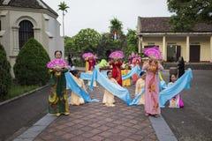 Ninh Binh,越南- 2015年5月16日:越南基督徒妇女进行在提供为母亲节的花的一个老传统舞蹈在 免版税库存图片