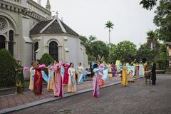 Ninh Binh,越南- 2015年5月16日:越南基督徒妇女进行在提供为母亲节的花的一个老传统舞蹈在 库存照片