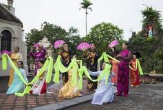 Ninh Binh,越南- 2015年5月16日:越南基督徒妇女进行在提供为母亲节的花的一个老传统舞蹈在 免版税库存照片