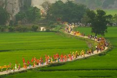 Ninh Binh, Vietnam - Apr 10, 2017: Thai Vi traditional spring festival with crowded people and palanquin, dancing dragon, flag...w. Alking on curved soil road Royalty Free Stock Images