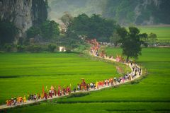 Ninh Binh, Vietnam - Apr 10, 2017: Thai Vi traditional spring festival with crowded people and palanquin, dancing dragon, flag...w. Alking on curved soil road Stock Images