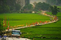 Ninh Binh, Vietnam - Apr 10, 2017: Thai Vi traditional spring festival with crowded people and palanquin, dancing dragon, flag...w. Alking on curved soil road Royalty Free Stock Image