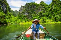 Ninh Binh, Vietnam - 02 Juni, 2013: Kvinnadrevet fartyget i floden Royaltyfri Foto