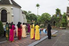 Ninh Binh, Vietnam - Maj 16, 2015: Vietnamesiska kristna kvinnor som bär den traditionella klänningen Ao Dai, utför ritual på lok royaltyfria foton