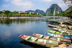 NINH BINH, VIETNAM: Massor av fartyg som väntar på turister för grotta, turnerar i Ngo Dong River på Tam Coc, Ninh Binh P Fotografering för Bildbyråer