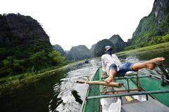 Ninh Binh, Vietnam - Oktober 14, 2010: Activiteit stroomafwaarts op boot met Vietnamees die voetpeddel en de berg van het menings Royalty-vrije Stock Fotografie