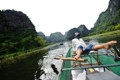 Ninh Binh, Vietnam - 14. Oktober 2010: Tätigkeit stromabwärts auf Boot mit dem Vietnamesen, der Fußpaddel- und Ansichtkalksteinbe Lizenzfreie Stockfotografie