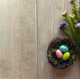 Ninho com os ovos coloridos na madeira envelhecida imagem de stock