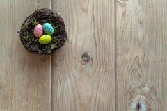 Ninho com os ovos coloridos na madeira envelhecida fotografia de stock royalty free