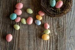 Ninho com os ovos coloridos na madeira envelhecida imagens de stock