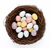 Ninho da cesta da Páscoa com os ovos de doces da Páscoa isolados na parte traseira do branco Foto de Stock Royalty Free