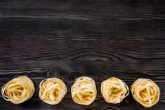 Ninho italiano do fettuccine da massa no copyspace de madeira cinzento da opinião de tampo da mesa imagens de stock