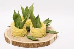Ninhos da massa com folhas de louro em um corte de madeira no fundo branco Fotografia de Stock