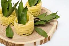 Ninhos da massa com folhas de louro em um corte de madeira no fundo branco Foto de Stock