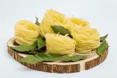 Ninhos da massa com folhas de louro em um corte de madeira no fundo branco Fotografia de Stock Royalty Free