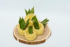 Ninhos da massa com folhas de louro em um corte de madeira no fundo branco Fotos de Stock