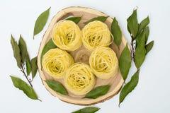 Ninhos da massa com folhas de louro em um corte de madeira no fundo branco Imagem de Stock