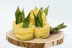 Ninhos da massa com folhas de louro em um corte de madeira no fundo branco Foto de Stock Royalty Free
