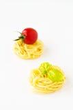 Ninhos da massa com tomate e manjericão de cereja Foto de Stock