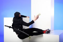 Ninja in black clothing catching dollar banknotes on white blocks. Isolated on blue royalty free stock photo