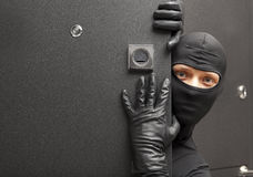 Ninja. Robber hiding behind a door Stock Image