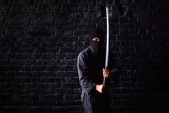 Ninja samurai with katana in attack pose on a dark brick wall background stock photo