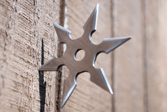 Ninja star. Silver ninja star embedded in wall stock photos
