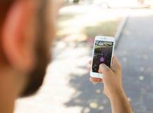 Nintendo Pokemon GO augmented reality smartphone. Empoli, Italy - July 26, 2016: Nintendo Pokemon GO augmented reality smartphone. The player in the park with Royalty Free Stock Photos