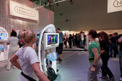 Nintendo's Booth and Wii. COLOGNE - AUGUST 20: Female Videogamers dancing and playing with Nintendo Wii at GamesCom 2011, the most important European video games Stock Images