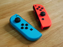 Nintendo Switch controllers on wooden table. stock image