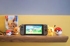 Nintendo Switch and Pokemon Let`s go Eevee and Pikachu stock photography
