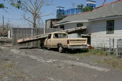 Ninth Ward Home and truck. After hurricane Katrian a pickup truck sits with a beam dropped on its hood next to heavily damaged home in the Ninth Ward of New Royalty Free Stock Images