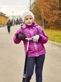Nio-år-gammal flicka som poserar med en sparkcykel i parkera Arkivbild