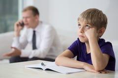 Niño aburrido que se sienta en el escritorio Foto de archivo libre de regalías