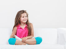 Niño alegre feliz de la niña que se sienta en el sofá Fotografía de archivo