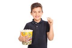Niño alegre que sostiene una caja grande de palomitas Imagen de archivo libre de regalías
