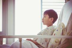 Niño asiático admitido en el sitio de hospital con el intrave de la bomba de la infusión Fotografía de archivo