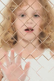Niño autístico enmascarado detrás del cristal del vidrio Imagenes de archivo
