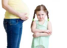 Niño celoso y su madre embarazada Foto de archivo libre de regalías