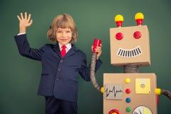 Niño con el robot del juguete en escuela Fotografía de archivo