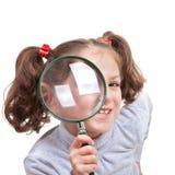 Niño con el vidrio de espía que magnifica Imagen de archivo