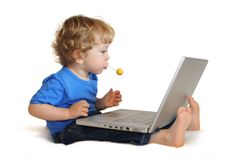 Niño con la computadora portátil y el lollipop Fotografía de archivo libre de regalías