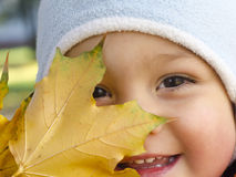 Niño con la hoja del otoño Imagenes de archivo