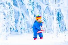 Niño con la pala de la nieve en invierno Fotografía de archivo libre de regalías